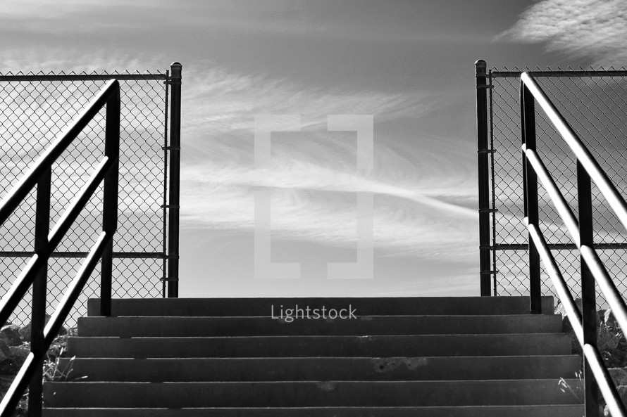 outdoor steps leading to a basketball court and wispy clouds in the sky in black and white