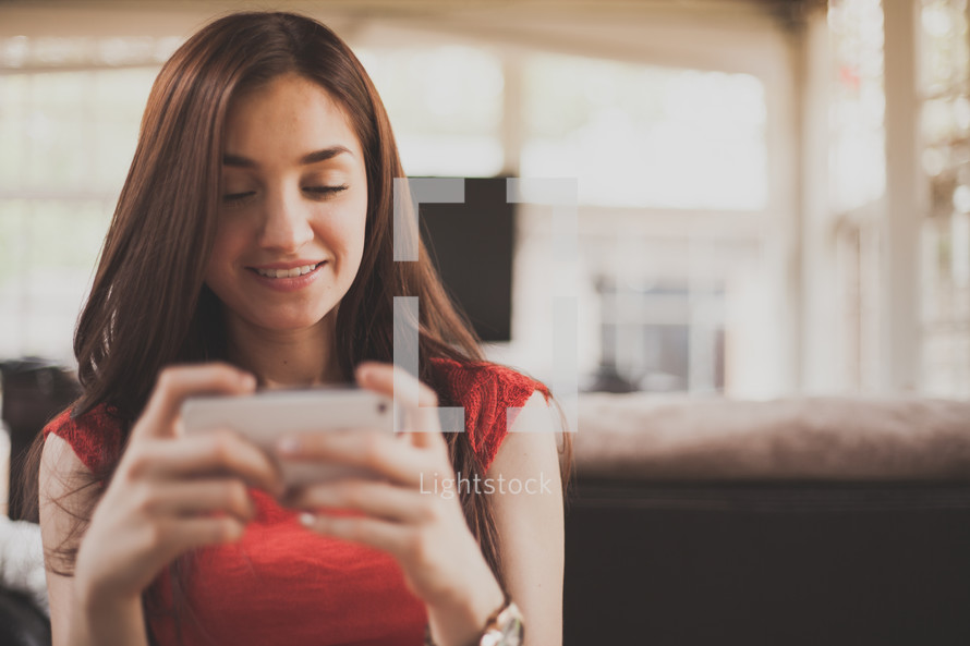 Smiling woman texting on a cell phone.