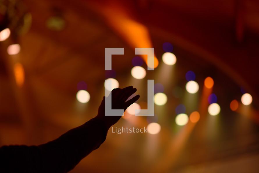 hand raised and stage lights