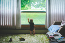 an infant boy looking out a window