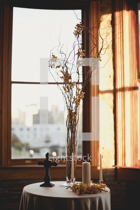 cross, vase and candles on table by a window
