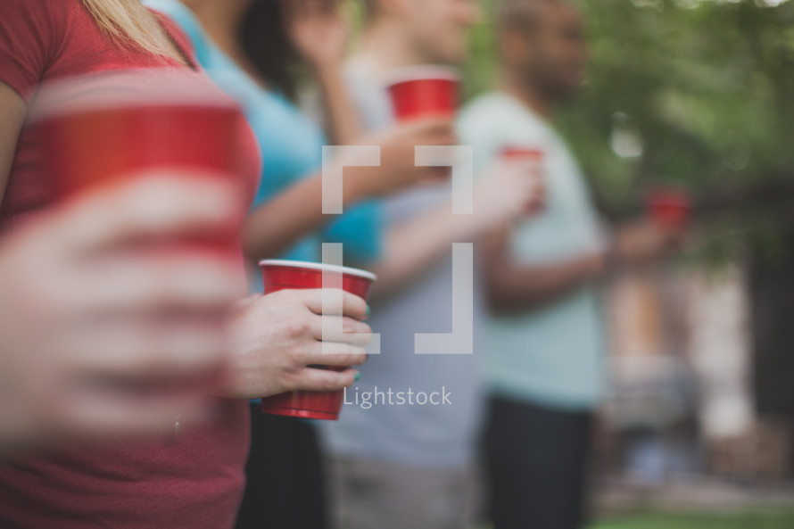 friends holding red solo cups at a gathering