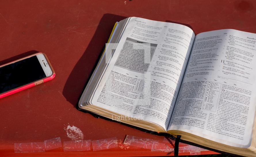 cellphone, and open Bible on a red table