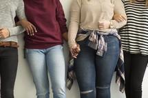 women standing arm in arm