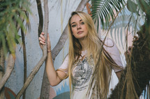 portrait of a blonde woman in a tropical plants