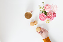 coffee, macaroons and pink flowers in a vase