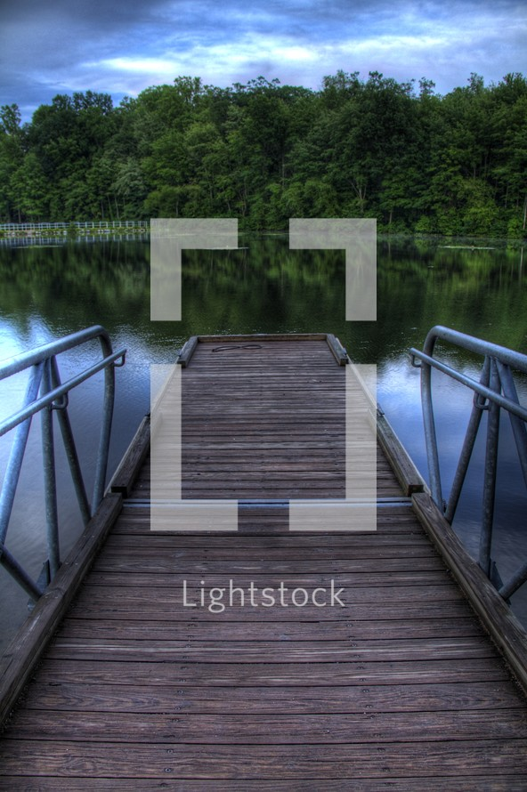 Wooden pier on the lake with reflection of the trees on the water.