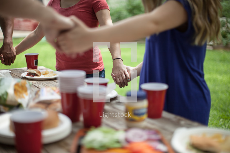 holding hands in prayer over a table of food a mealtime