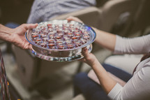 passing a tray of communion wine cups