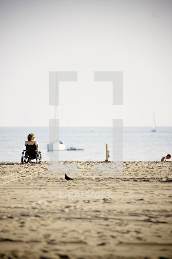woman in a wheel chair on the sandy beach shore watching boats