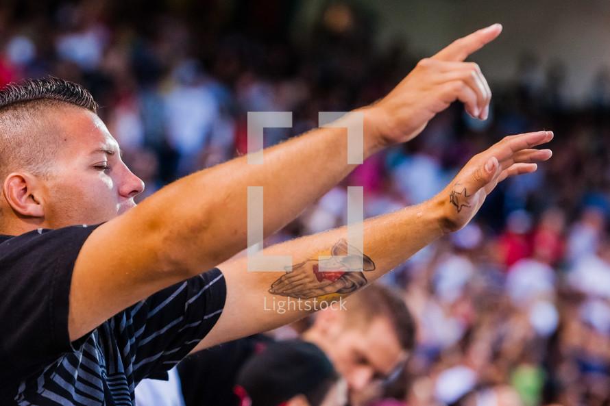 Praising God man hands raised lifted tattoo worship eyes closed