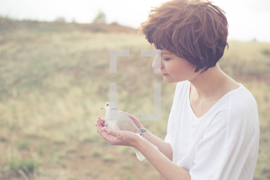Woman standing in a field holding a dove.
