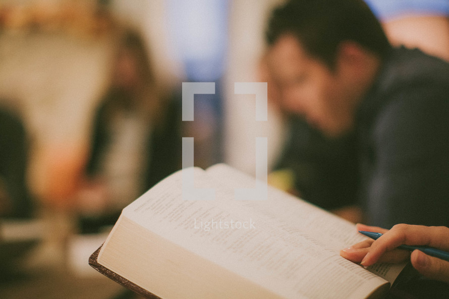 hand holding a pen and an opened Bible