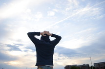 A person stands looking at the sky with hands behind his head.
