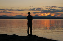 Silhouette of a man standing before a lake at dusk.