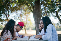 friends reading Bibles together outdoors