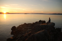 Silhouette of a man sitting on a rock formation in the ocean water at sunset.