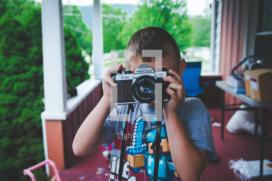a boy child taking a picture with a camera