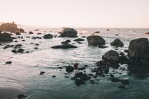 a man walking on rocks on a beach