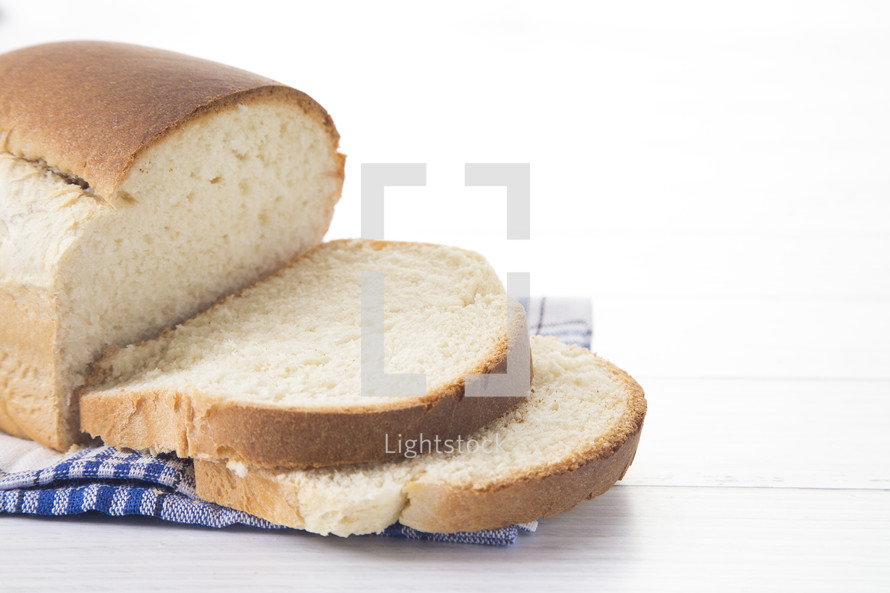Freshly Baked Loaf of Homemade White Bread Sliced on a White Table