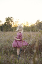 a toddler girl twirling her dress in tall grasses