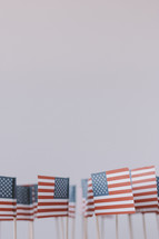 A group of small American flags on a white background.