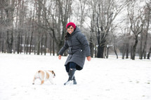 a smiling woman playing in snow with a bulldog