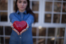 A woman's hands holding out a red heart