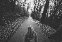 woman standing in the middle of a paved path