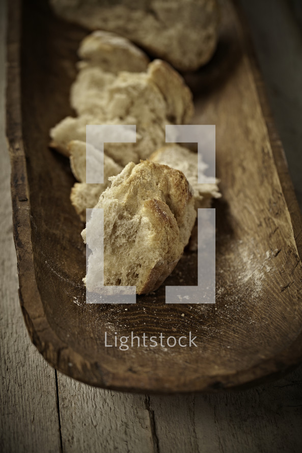 Broken pieces of bread on a wooden tray
