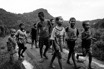 young barefoot boys walking on a dirt road