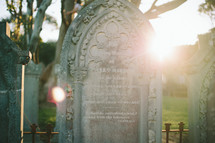 Sun shining on an ornate tombstone in a cemetery.