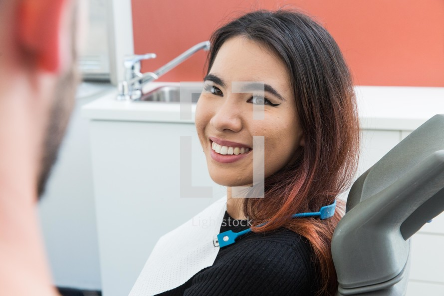 a smiling woman in the dentist chair