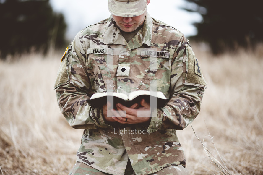 Christian soldier kneeling in a field praying holding a Bible