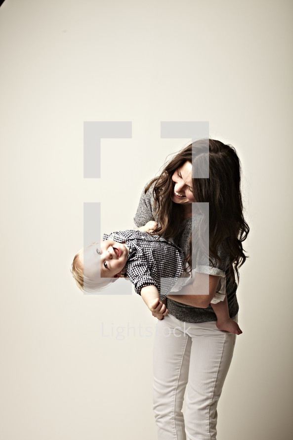 A little boy laughing in his mother's arms isolated on white