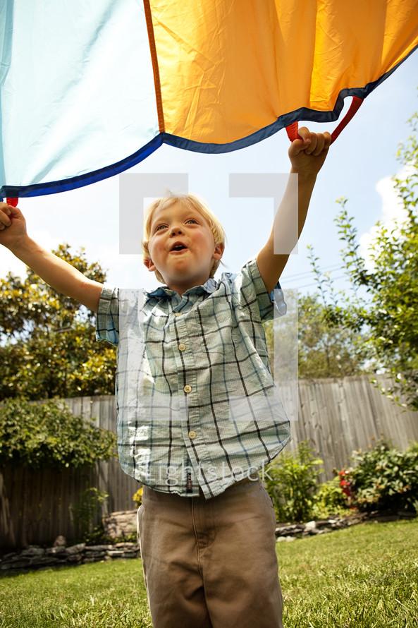toddler boy holding a parachute