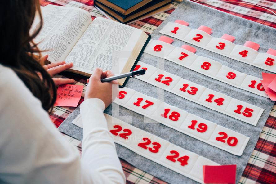 a woman stuffing Bible verses into an Advent calendar