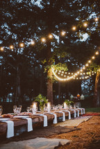 An outdoor table set for a dinner party, lit by strings of lights.