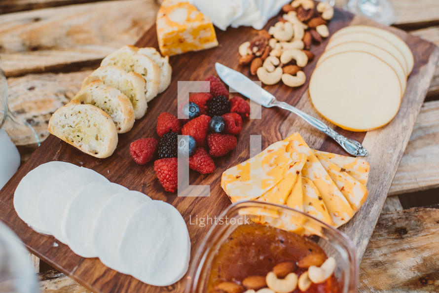 A wooden cutting board covered with a variety of appetizers.