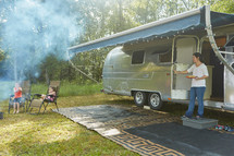 roasting hotdogs near a camper