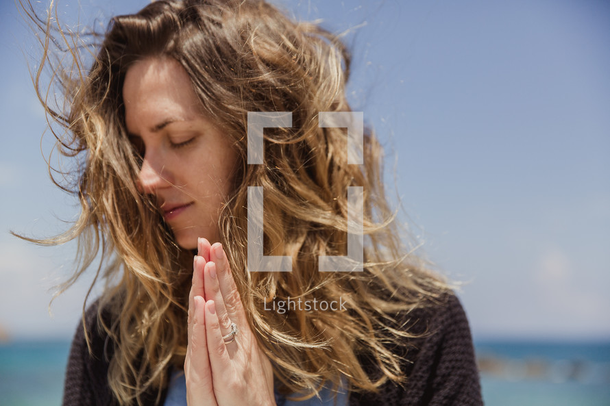 woman in prayer at the Coast in Greece