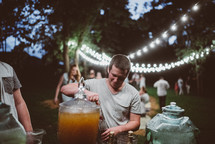 people gathered for an outdoors dinner party pouring drinks