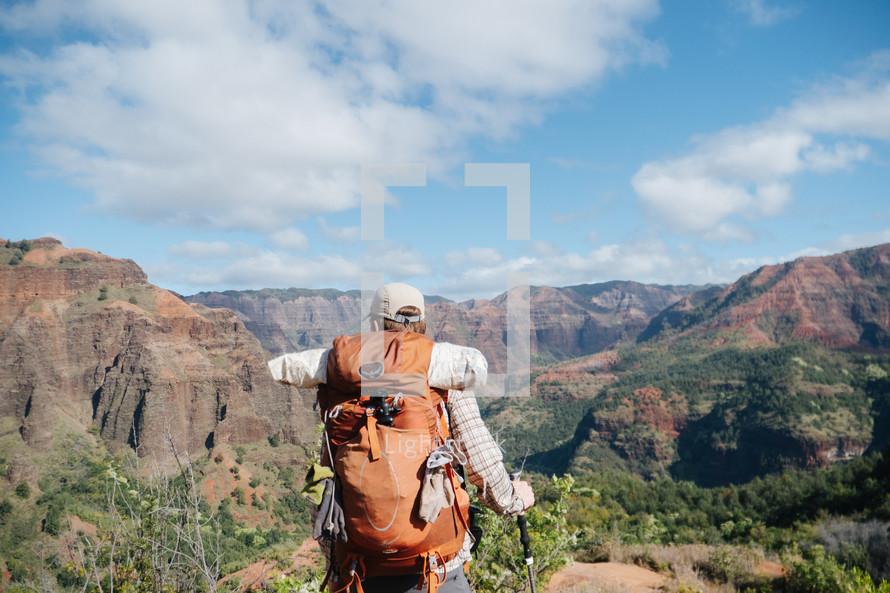 a man backpacking through a mountainous landscape
