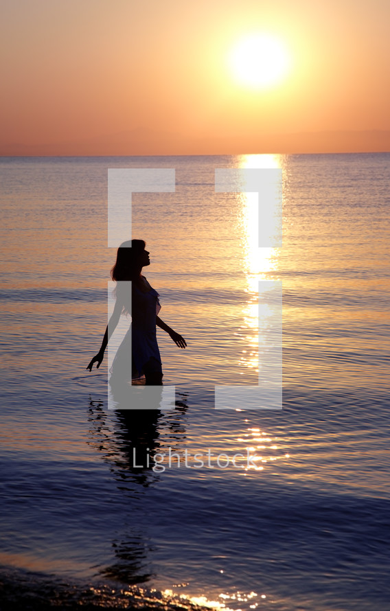 a woman standing in the ocean at sunset
