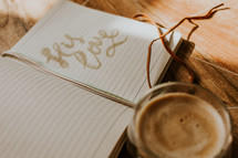 clear glass coffee cup and pages of a journal