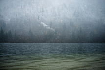 snow falling over a lake