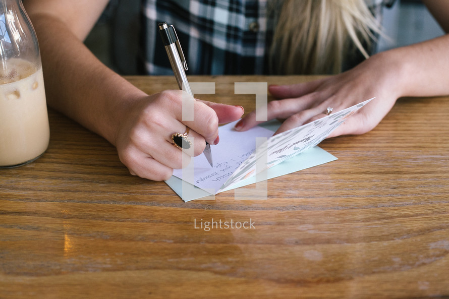 a woman writing a thank you note