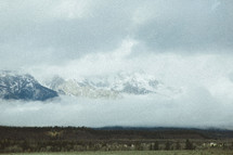 fog and low hanging clouds and a mountain peak