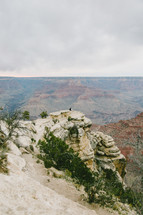 people sitting at the edge of a cliff looking out over a canyon