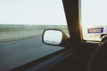 rear view mirror of a car on a road trip